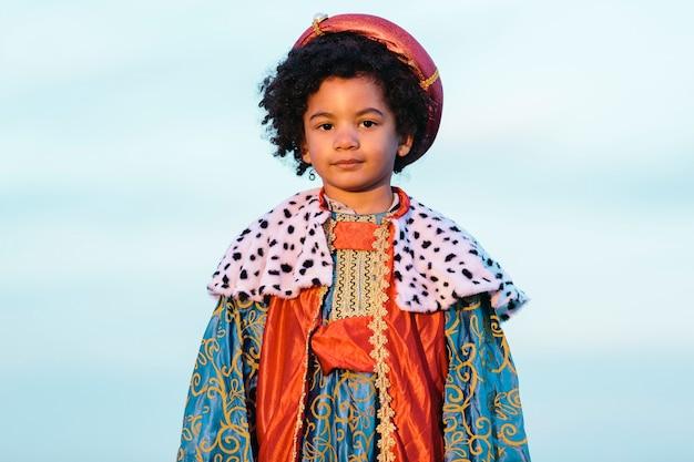 賢い男の衣装を着たアフロヘアーの黒人の子供。カメラを見てください。空の背景に。ミディアムショット。子供とクリスマスのコンセプト。