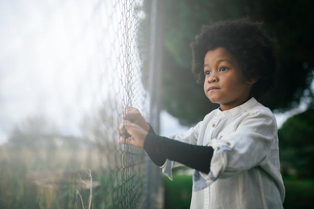劇的で悲しい表情で、フェンスを握って、アフロ髪の黒人の子供