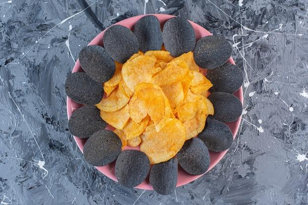 Черные чипсы и картофельные чипсы в тарелке, на мраморной поверхности