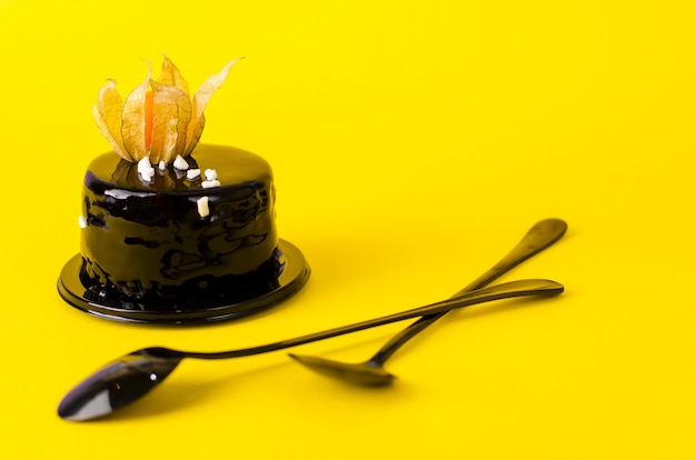 Black chocolate cake topped with black velvet icing decorated with physalis.