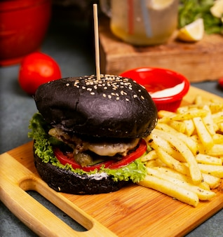 Black chocolate pan beef cheese burger with vegetables fast food, french fries and ketchup