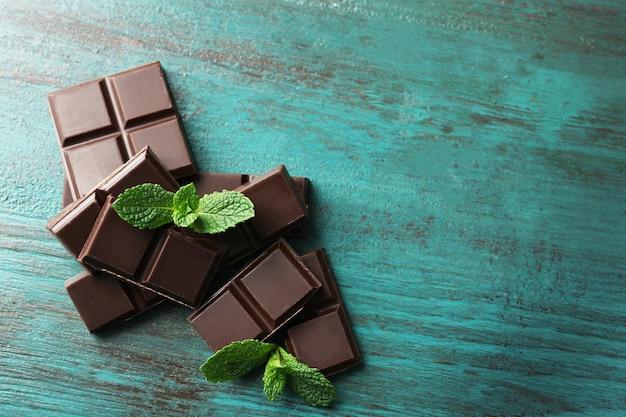 カラーの木製の表面にブラックチョコレートのかけら