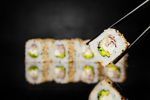 Black chopsticks holding roll philadelphia made of tuna, cucumber, nori