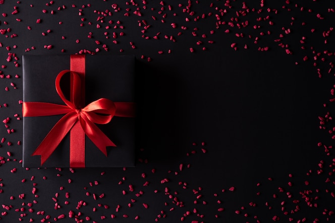 Black christmas boxes with red ribbon on black background.