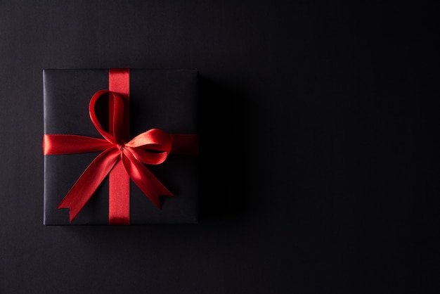 Black christmas boxes with red ribbon on black
