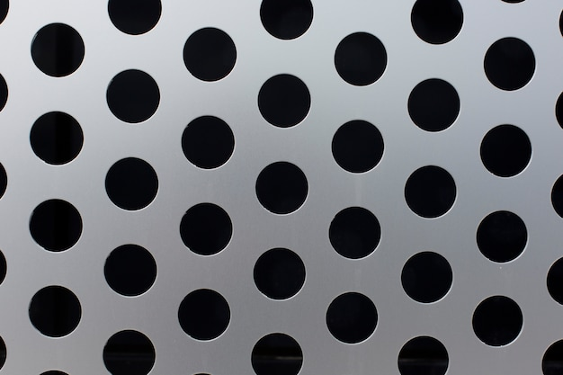 Black circles on a metal surface  texture background