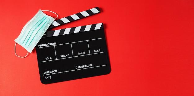 검은색 클래퍼 보드와 얼굴 마스크는 빨간색 배경에 있습니다. 비디오 제작이나 영화 및 영화 산업에서 사용됩니다.