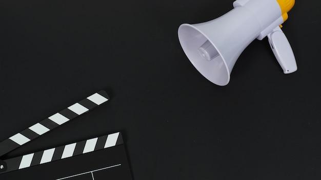 黒のカチンコまたは映画のカチンコまたはスレートと黒の背景のマガフォン。ビデオ制作や映画業界で使用されます。