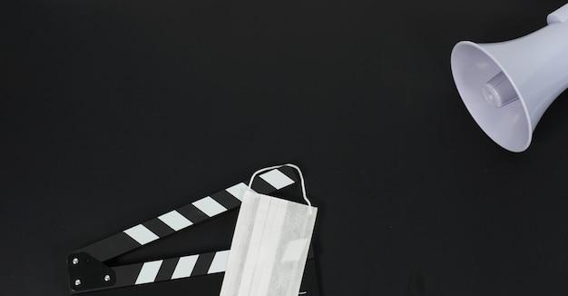 黒のカチンコまたは映画のスレートとフェイスマスク、黒の背景にマガフォン。ビデオ制作や映画業界で使用されます。
