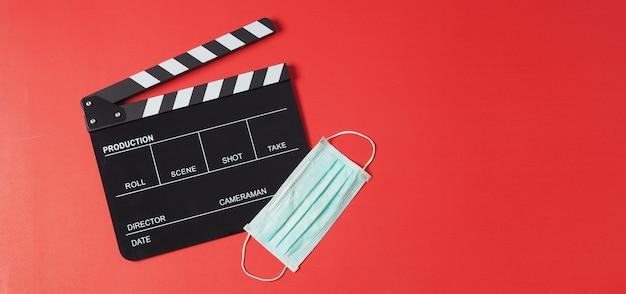 검은색 클래퍼 보드 또는 영화 슬레이트와 빨간색 배경의 안면 마스크. 비디오 제작이나 영화 및 영화 산업에서 사용됩니다.