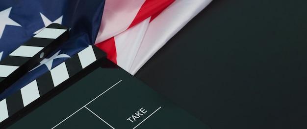 검은색 클래퍼 보드 또는 영화 슬레이트와 아메리카 합중국(usa.)의 국기가 검정색 배경에 있습니다.