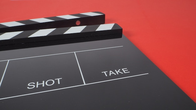 Black clapperboard or movie slate. it use in video production or film and cinema industry on red background.