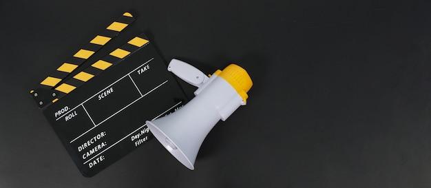 검은색 clapperboard 또는 영화 슬레이트와 검은 배경에 확성기.
