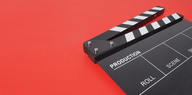 Черный с 'хлопушкой' или сланец для фильмов или доску с 'хлопушкой' на красном фоне. он используется в производстве видео и киноиндустрии.