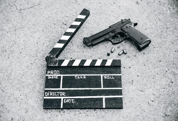 背景に銃を持つ黒いカチンコ。映画の監督と撮影。探偵の刑事物語。