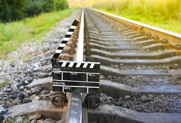 背景に線路のある黒いカチンコ。映画の監督と撮影。旅行の話。