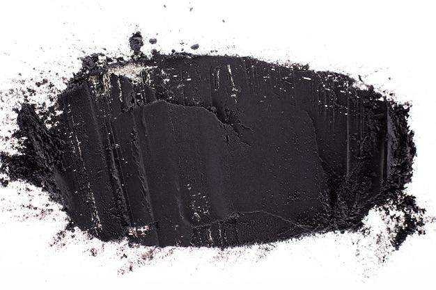 Порошок черной глины на белом фоне