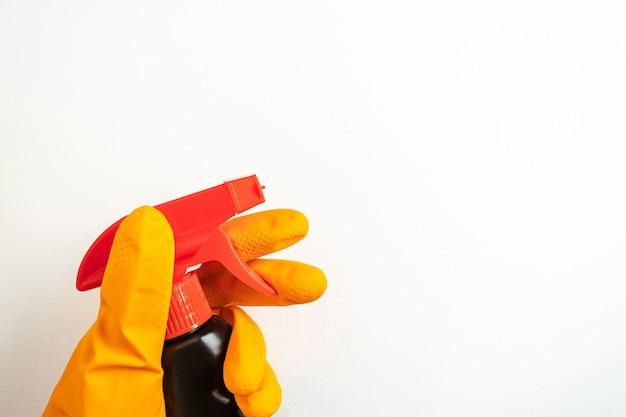 Черный очищающий спрей в руке в оранжевой перчатке на белом фоне. концепция уборки, чистоты и бытовой химии