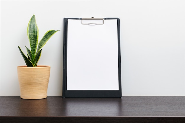 Black clipboard mockup wtih cactus in a pot on dark workspace table and white background