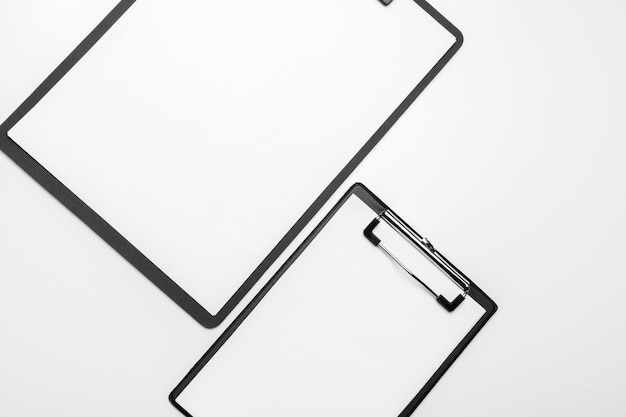 Black clipboard with blank white sheet attached on white