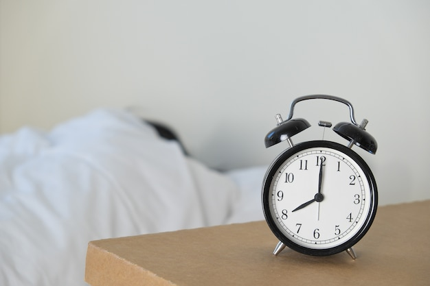 A black clock on brown table with a person on a white bed background