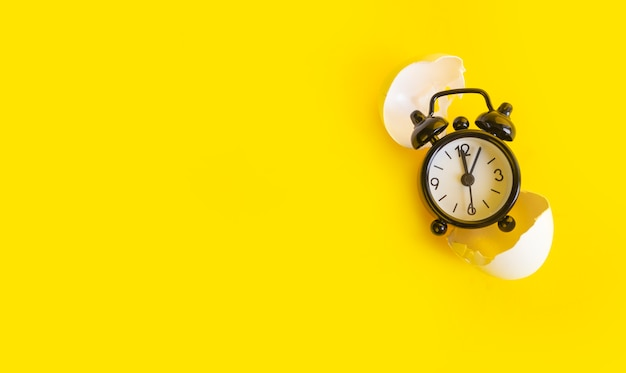 Black clock on a yellow in an egg shell