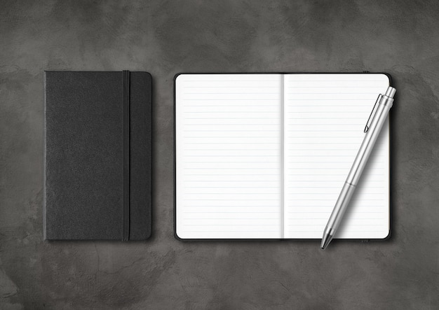 Черные закрытые и открытые записные книжки с ручкой. изолированные на темном бетоне