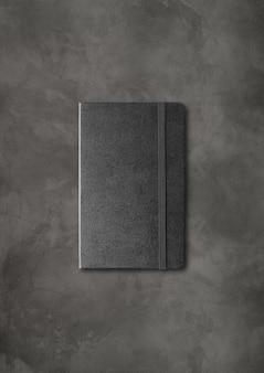 Black closed notebook mockup isolated on dark concrete