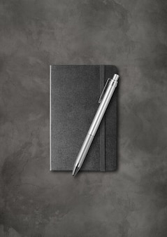 Black closed notebook with a pen.  isolated on dark concrete background