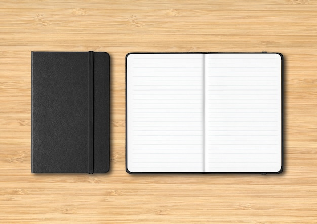 Black closed and open lined notebooks mockup isolated on wooden background