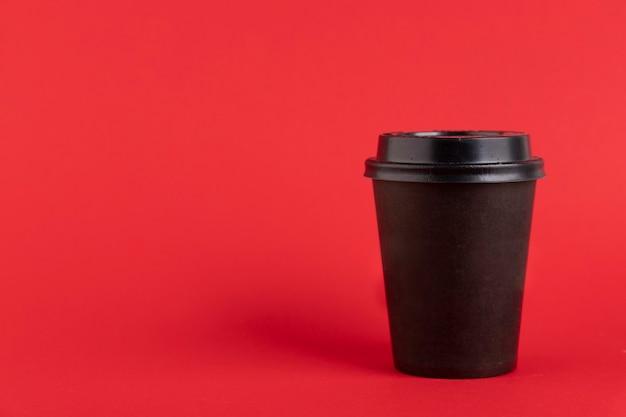 赤い背景のコーヒーやお茶のための黒い閉じたプラスチック、紙コップ。スペースをコピーします。