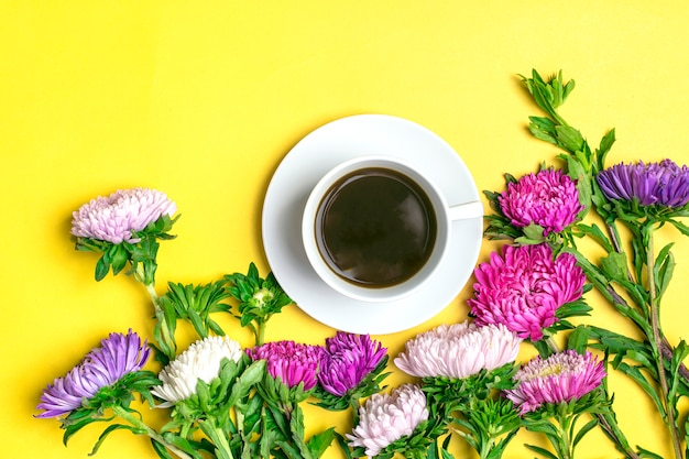Black coffee americano in white cup and flowers asters on yellow background flat lay