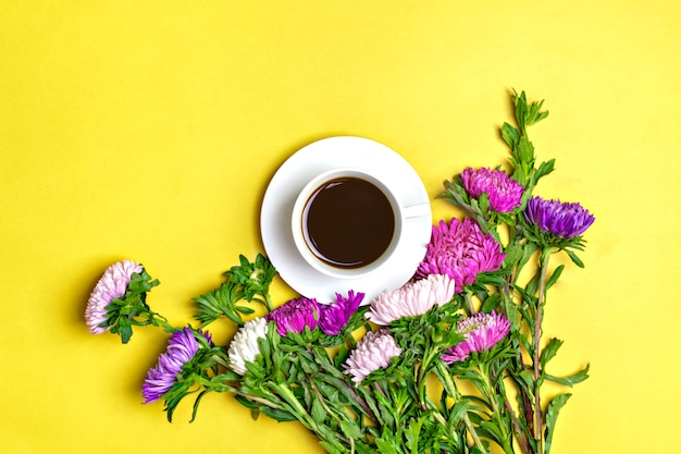 Black coffee americano in a white cup and flowers asters on a yellow background flat lay