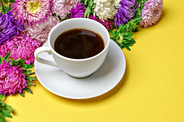 Black coffee americano in a white cup and flowers asters on yellow background flat lay