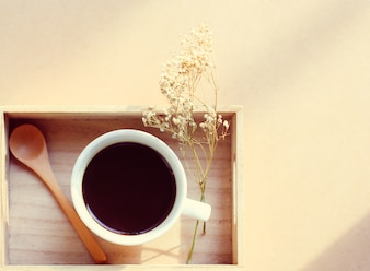 Black coffee and spoon on wooden tray with dried flower, retro filter effect