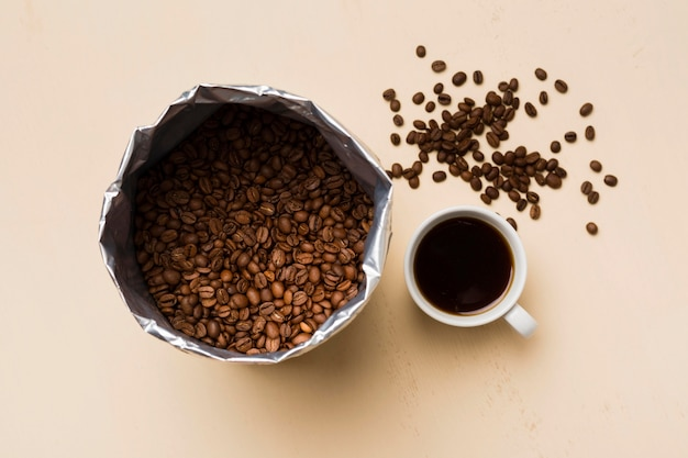 Black coffee beans arrangement on beige background with cup of coffee