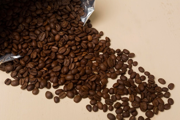 Black coffee beans assortment on beige background