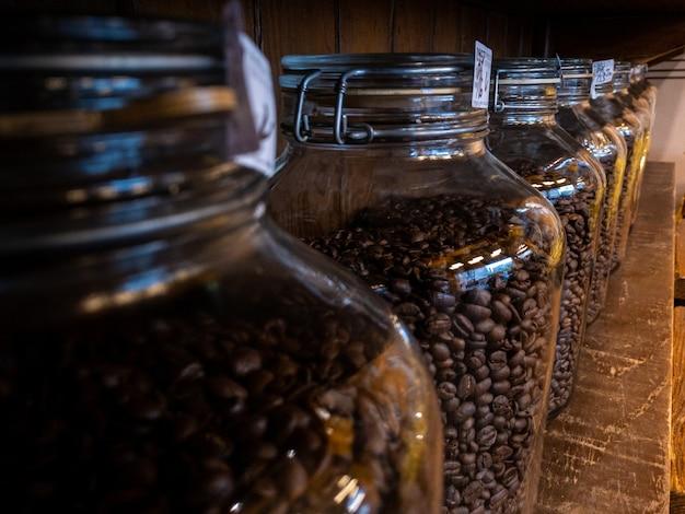 カフェショップの背景にある木製スタンドのブラックコーヒー豆ガラス瓶包装パッケージ。ハウスボトルに焼きたてのカフェビーンズ。