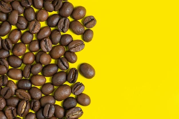 黄色の背景に黒のコーヒー豆。左側の垂直位置オブジェクト、右側のテキスト用のスペースをコピーします。カラフルなコーヒーの静物のクローズアップ、フラットレイビュー。