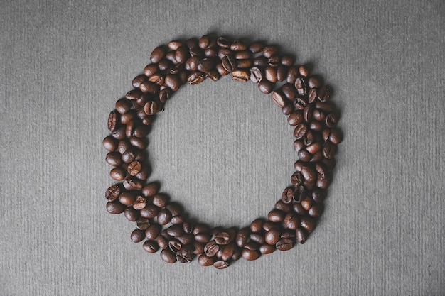 Black coffee beans shaped like a circle on grey background