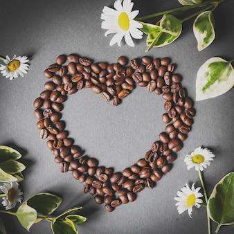 Black coffee beans shaped like a heart with flowers on grey background top view