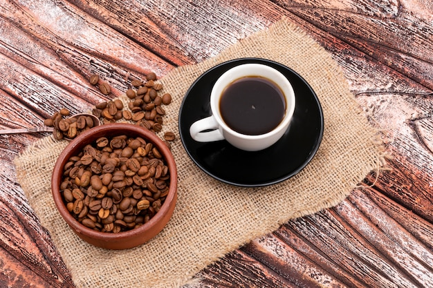 Black coffee and coffee beans on sackcloth wooden surface top view