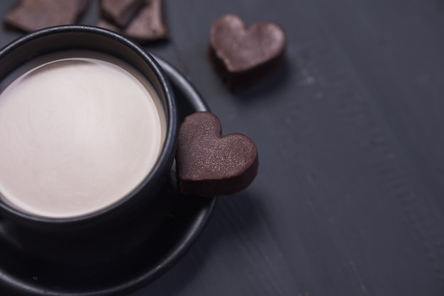 Черная кофейная чашка и шоколадное печенье в форме сердца на темном фоне. выборочный фокус. копировать пространство