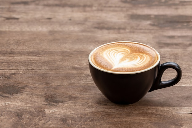 Black coffee cup of art latte with froth heart shaped  on wooden table. copy space for text design.