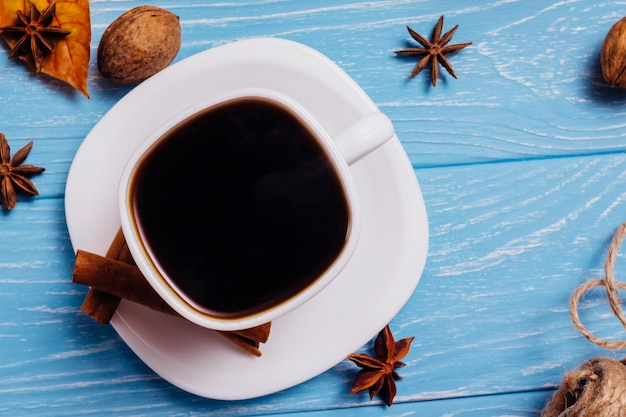 Black coffee in a cup on a blue wooden table. top view