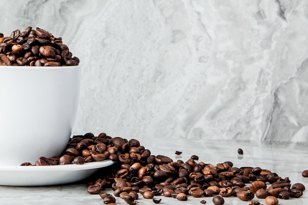 Black coffee in cup and coffee beans on marble background. top view, space for text
