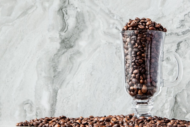 Black coffee in cup and coffee beans on marble background. top view, space for text.