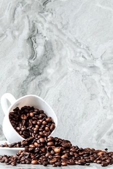 Black coffee in cup and coffee beans on marble background.