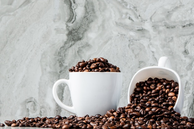 Black coffee in cup and coffee beans on marble