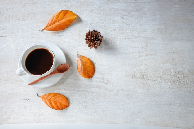 Black coffee cup and dried leaves on a white background.